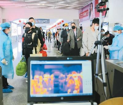 2月11日,医务人员在广西壮族自治区钦州东站出站口布设5G热成像测温设备检测体温。   曾开宏摄(人民图片)